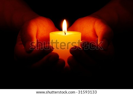 Heart-shaped hands holding yellow candle in dark - stock photo