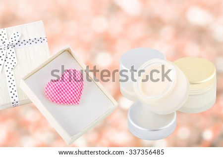 Heart-shaped in decorative gift box with moisturizing face cream on the bokeh background-Valentine's Day,New Year-Beauty concept