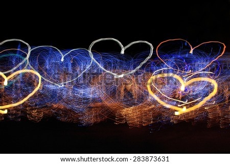 heart shaped light trails on a black background - stock photo