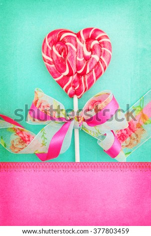 Heart shaped lollipop for Valentine's Day with turquoise background. Copy space background - stock photo