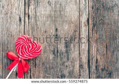 Heart shaped lollipop on background wooden. (Old color tone image)