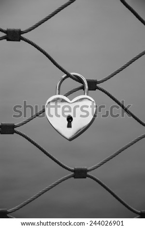 Heart shaped love padlock in Paris. Valentine's day background. Aged photo. Black and white. - stock photo