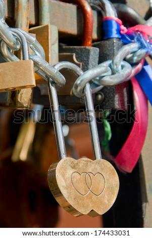 Heart shaped padlock fastened to the railing - stock photo