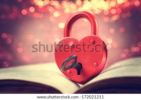 Heart-shaped padlock with key on open book - stock photo