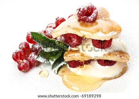 Heart shaped pancakes topped with honey, raspberries, mint and Powdered sugar on white background - stock photo