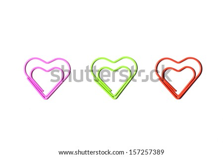 Heart shaped paper clip in 3 colors next to each other - stock photo