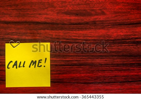 Heart shaped paper clip on a yellow sticky note with the words Call me written on it. - stock photo