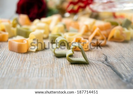 heart shaped pasta with rose in the background - stock photo