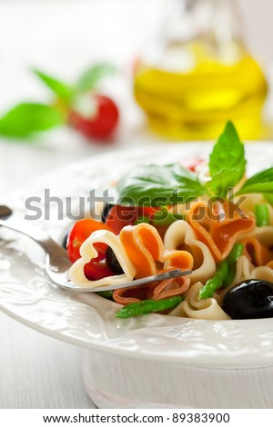 Heart-shaped pasta with tomatoes, asparagus and olives