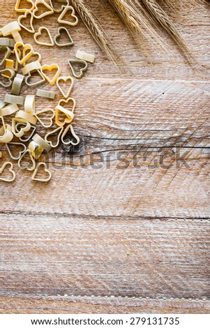 Heart shaped pasta with wheat ears on a wooden textured table - stock photo