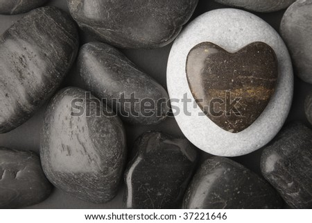 Heart shaped pebble framed on a dark pebble background - stock photo