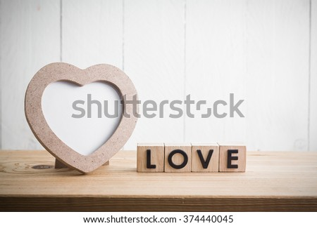 "Heart shaped photo frame with ""love"" in cube on wood table - stock photo"
