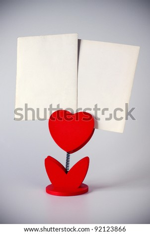 heart-shaped photo holder holding two blank photos
