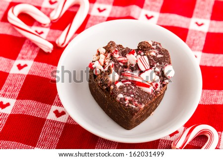 Heart shaped piece of homemade peppermint fudge on small round white plate with candy canes