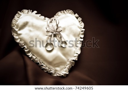 heart-shaped pillow with wedding rings - stock photo