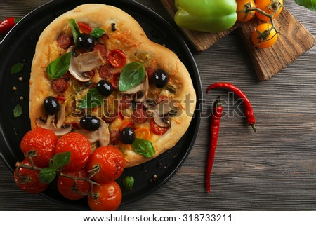 Heart shaped pizza on metal tray on wooden table