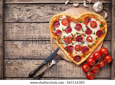 Heart shaped pizza with pepperoni, tomatoes and mozzarella on vintage wooden table background. Valentines day love concept.  - stock photo