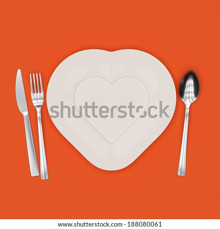 Heart-shaped plate with fork, knife and spoon - stock photo