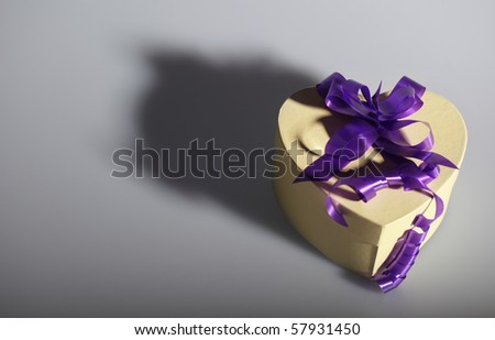 Heart shaped present box with ribbon - stock photo