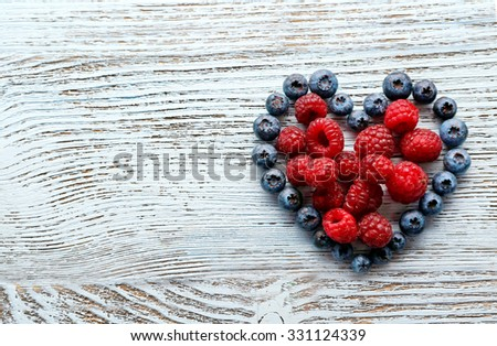 Heart shaped raspberries and blueberries on old wooden background - stock photo