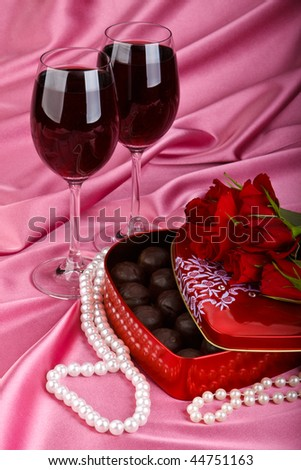 heart shaped red box with sweets two glasses of red wine and bunch of