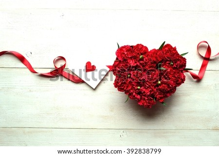 Heart shaped red carnation flower arrangement with message card.Image of Mothers day - stock photo