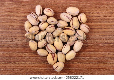 Heart shaped roasted pistachio nuts on natural wooden table background, healthy food and nutrition, symbol of love