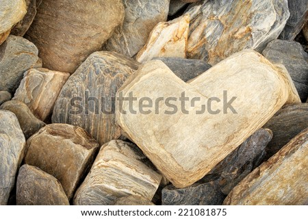 Heart shaped stone among other limestones - Symbol of Eternal Love, Valentine's Day concept - stock photo
