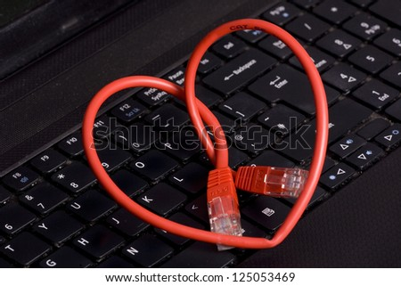 heart shaped thernet cable on a laptop - stock photo