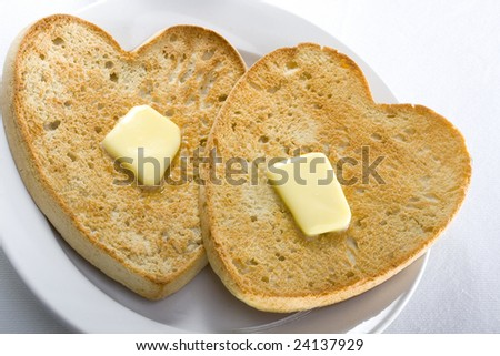 Heart shaped toast with butter on a plate, white table cloth background. - stock photo