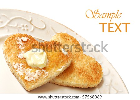 Heart shaped toast with butter on decorative antiqued plate.  White background with copy space. - stock photo