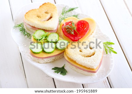 Heart shaped toasts with ham and cheese - stock photo