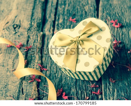 Heart shaped Valentines Day gift box on wood. - stock photo