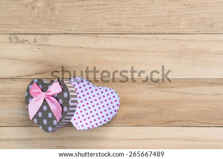 Heart shaped Valentines Day gift box on wooden background. - stock photo