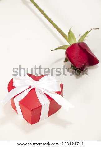 Heart-shaped Valentines Day gift box with rose over a white background