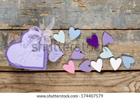 Heart shaped Valentines Day present gift box with small hearts around it on old wood.