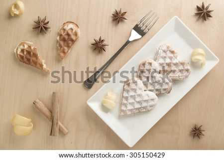 Heart shaped waffles with lemon zest garnished with powdered sugar served on rectangular plate on light wood table, a broken heart waffle, fork, cinnamon rolls, lemon zest and star anise by the side - stock photo