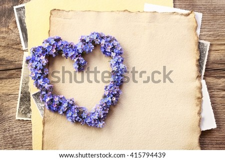 Heart shaped wreath made of forget-me-not flowers. Vintage sheets of paper, copy space. - stock photo