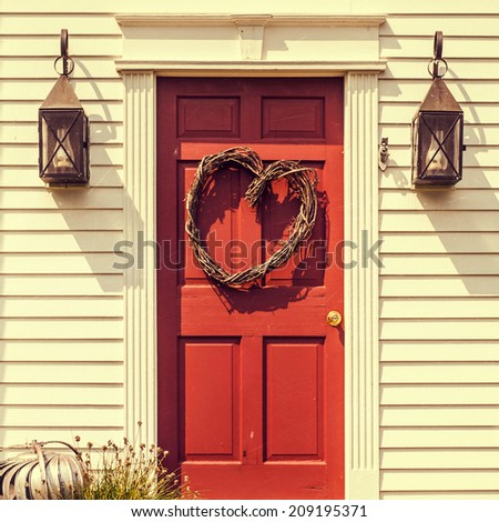 Heart shaped wreath on red door - stock photo