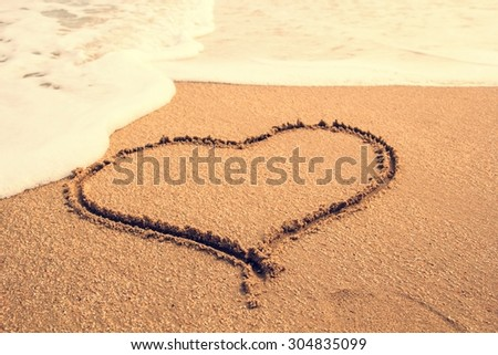 Heart-shaped write on sand beach under blue sky and ocean view.