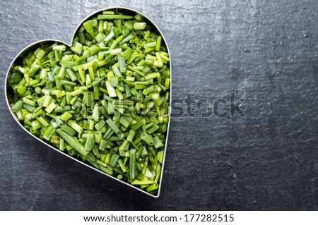 Heart shapes filled with fresh cutted Chive (I love herbs concept) - stock photo