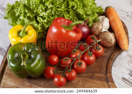 Heart sign made of cherry tomatoes on the wooden board - stock photo