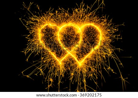 heart sparkle, Valentines Day Hear gold color. Sparklers heart,  Heart of sparklers on black background,love and light.  - stock photo