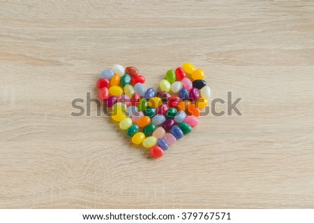 Heart symbol from jelly beans on wooden background - stock photo