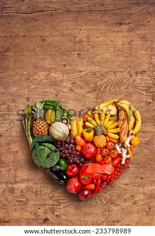 Heart symbol. Fruits diet concept. Healthy eating concept / food photography of heart made from different fruits and vegetables on old wooden table  - stock photo