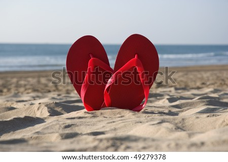 Heart symbol made of red flip flops on the beach - stock photo