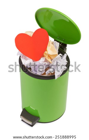 Heart thrown in the trash. The concept of separation, termination of a romantic relationship. The loss of love. Isolated on white