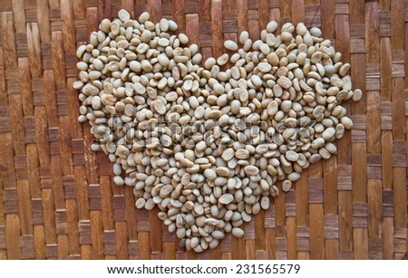 Heart with coffee beans on bamboo flooring. - stock photo
