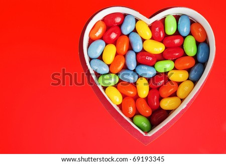 Heart with Colorful Jellybean Candy on a Bright Red Background - stock photo