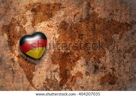 heart with national flag of germany on a vintage world map crack paper background. concept - stock photo